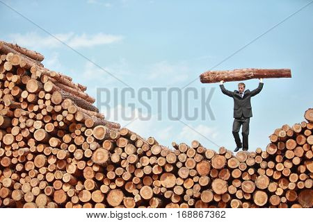 Hardworking Business Man on top of large pile of logs lifting heavy log - front view