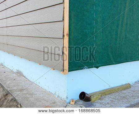 Plastic Siding Wall Construction and Insulation Membrane on House Exterior Wall. Wall Insulation.