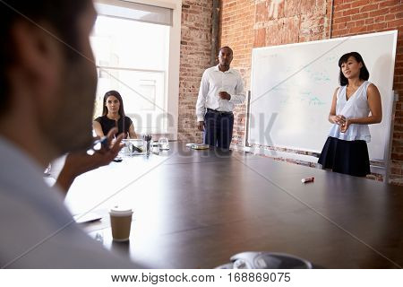 Businesspeople At Whiteboard Giving Presentation In Boardroom