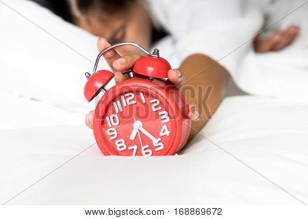 Irritated young woman putting her alarm clock off in the morning lazy wake up in morning. Relaxing concept.