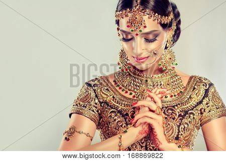 Portrait  smiling of beautiful indian girl. Young hindu woman model with golden kundan jewelry set . Traditional Indian costume lehenga choli
