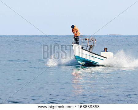 Nahariyya Israel - February 04 2017 : Fishermen in overcast weather patrol on boat and looking for fish near the shore of Nahariyya Israel