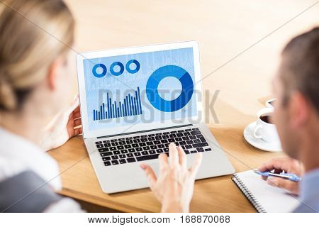 Blue data against business people working together while using laptop