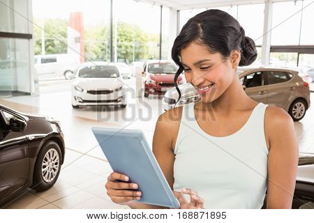 Smiling businesswoman using digital tablet against view of row new car