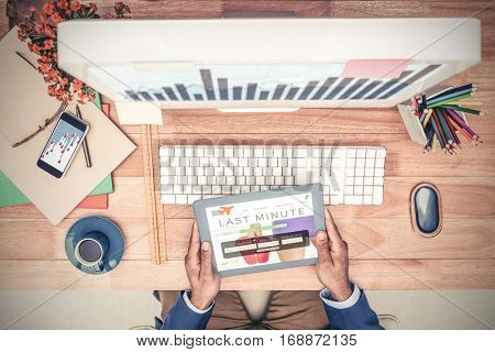 Businessman holding digital tablet while sitting at computer desk against holidays booking app