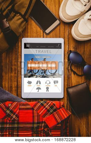 Tablet shirt jean shoes smartphone wallet and bag against holidays booking app