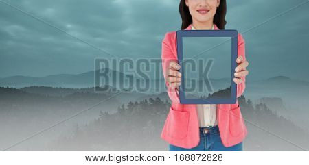 Elegant brunette using tablet against trees and mountain range against cloudscape