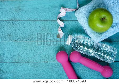 Fitness equipment. Nutrition food on turquoise wooden background.