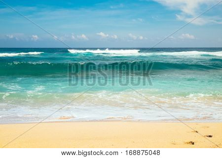 Close up photography of colorful sea wave with sunny blue sky on horizon at Bali island, indonesia. Outdoor nature landscape of big ocean waves and clear white sand beach in Southeast Asia.