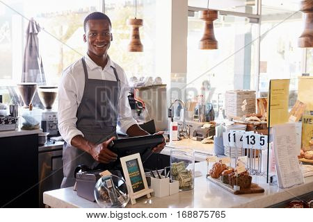 Portrait Of Male Employee Working At Delicatessen Checkout