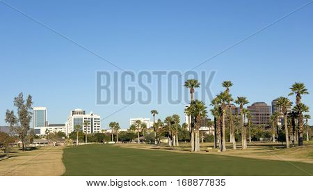 A green lawn stretching fromEncanto park to downtown of Phoenix Arizona; Copy space in clear blue sky
