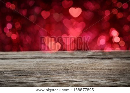 Empty of wood table top with blurred heart bokeh background.