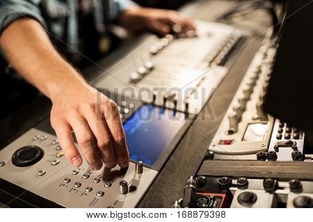 music, technology, people and equipment concept - man using mixing console in sound recording studio