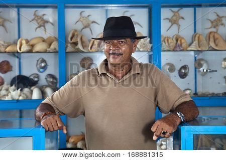 Thе owner a shop of Souvenirs made from sea shells on the ocean beach in Sri Lanka