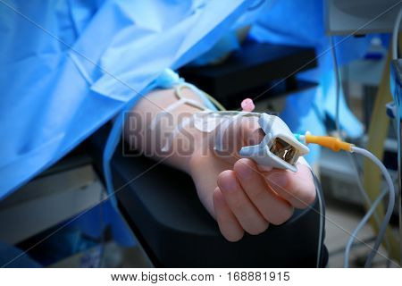 Patient with pulse oxymeter in operating room, closeup