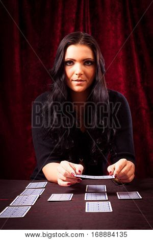 Studio shot of friendly fortune teller with tarot cards