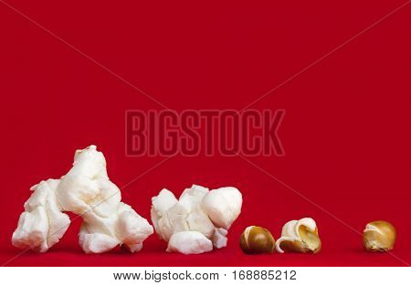 Popcorn over vibrant red background.  Closeup of popped and unpopped corn kernels. Side view. Very large file.