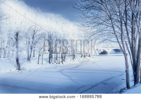 Landscape with frozen river in the winter snow and trees blue sky bridge far away