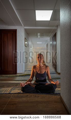 Young woman doing yoga at the office sand and waves on the floor and clouds in the sky concept of stress and relaxation