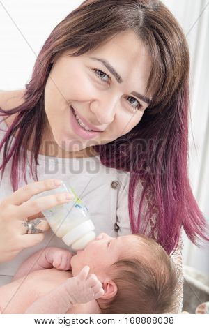 Modern Young Mother Giving Milk To Her Baby From Bottle