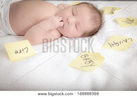Post It Stickers Placed Around Carefree Newborn Baby On Bed