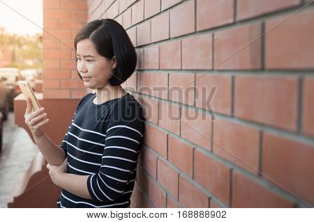 Weekend activity scene of adult Asian woman using mobile phone while standing beside brick wall. Urban lifestyle on with technology.