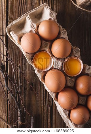 Eggs and broken eggs and quail eggs in the package on a wooden background. Rustic Style. Eggs. Easter photo concept. Copyspace