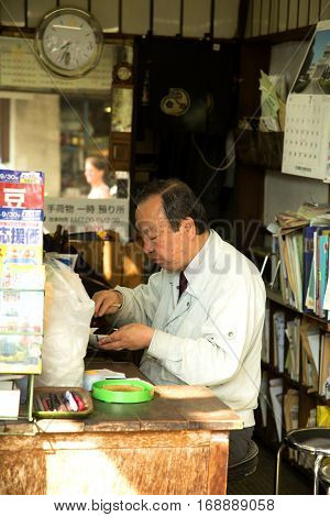 TOKYO-JAPAN, 27 June 2016: Japanese man having a break in the backstore of his store at tsukiji fish market in Tokyo, japan. The biggest wholesale fish and seafood market in the world.