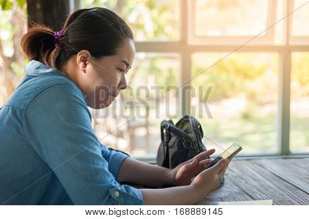 Young hipster Asian woman woker concentrate on mobile phone for social network activity. online working activity with mobile device.