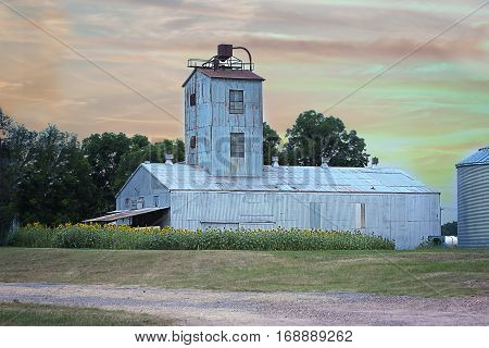 Old cotton gin with sunflower patch on dirt road