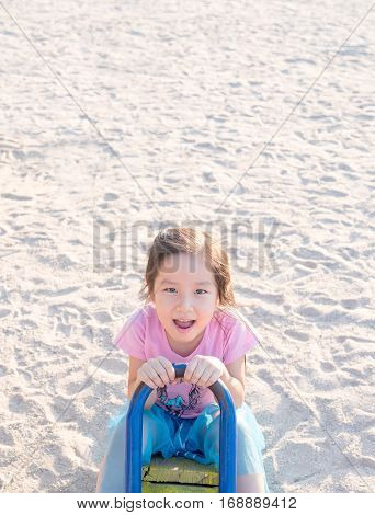 happy Asian child on a seesaw in sunset lightsand background