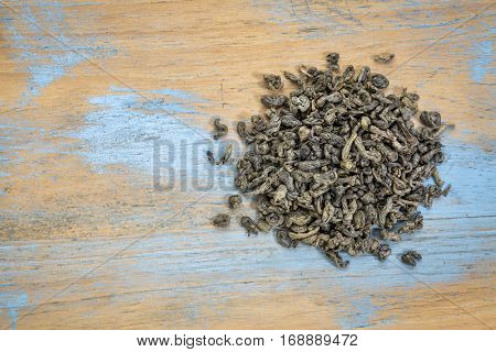 loose leaf Chinese gunpowder (pearl) green tea, a heap over grunge wood with a copy space, top view