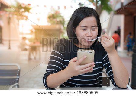 Weekend lifestyle scene of adult Asian woman eating dessert while using mobile phone at coffee shop. Urban lifestyle on weekend with technology.