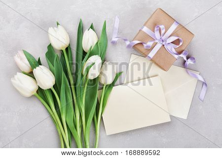 Spring tulip flowers gift box and paper card on gray stone table from above in flat lay style. Greeting for Womens or Mothers Day.