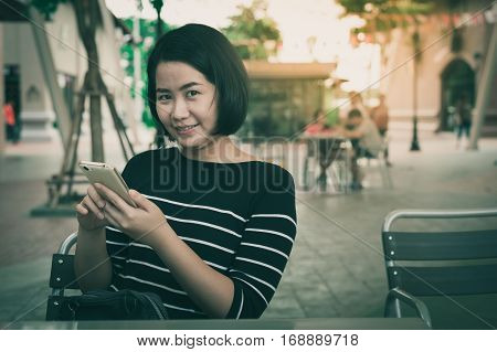 Weekend activity scene of adult Asian woman using mobile phone at coffee shop with vintage filter effect. Urban lifestyle with technology concept.