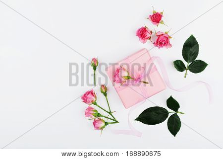 Gift or present box and rose flower on white table top view in flat lay style for greeting card on Womans day.