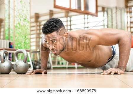 African american man pushups chest exercise and gritty serious facial expression inside gym - Attractive black guy shirtless body training muscles on the floor - Concept of sports and fitness indoor