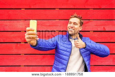 Handsome man taking selfie against red wooden wall in London square. Travel adventure lifestyle around word destination. Multicolored photo with young guy making thumbs up for sending pic to friends.