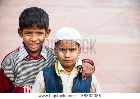 Agra India - 2015 January 10 : Two young boys one wearing a muslim taqiyah in the Jama Masjid mosque courtyard of Agra India