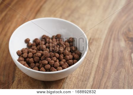 chocolate cereal balls in white bowl for breakfast, shallow focus