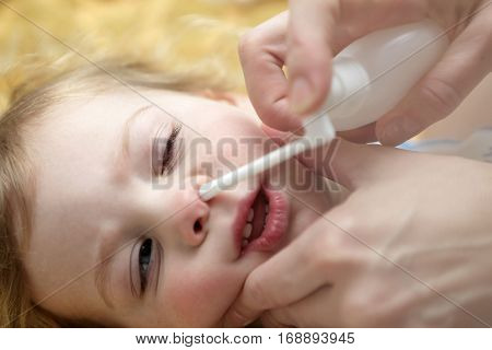 Child Inhaling Nasal Spray on bed at home