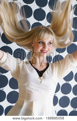 Attractive blonde model girl with a thick hair shakes your head and smiles for camera at the beauty salon