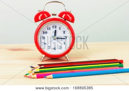 back To School. Colored Pencils And An Alarm Clock,