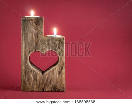Lit romantic wooden candle holder with cut heart over red background