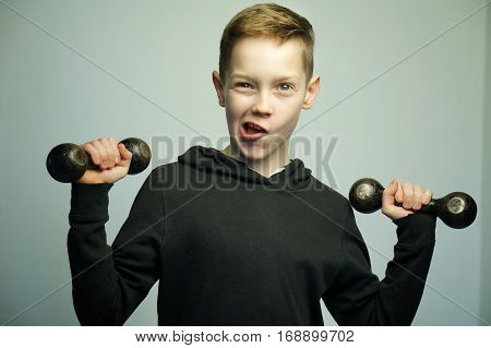 Portrait of a handsome teenage sport boy with dumbbells and stylish haircut, softbox lighting studio shot.