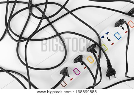 Maximum electrical cords plugs connected electrical power strip or extension block with messy wires top view on white background messy electric equipment flat lay concept.
