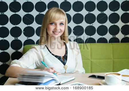 Blonde girl writes important information in a diary and looks at a computer tablet during a coffee break