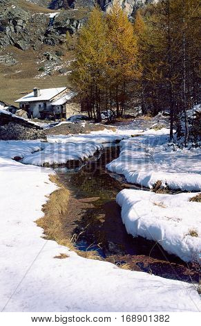 Mountain chalet pines river and snow Savoy France