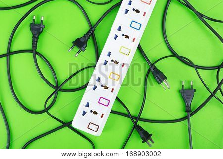 Messy of electrical cords plugs and wires unconnected electrical power strip or extension block with messy wires top view on colorful background messy electric equipment flat lay concept.