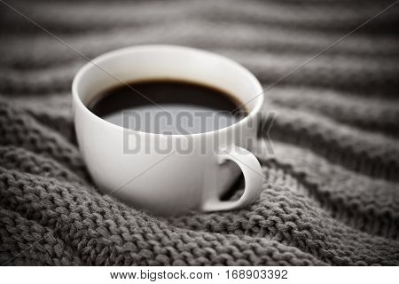 Cup of coffee on knitted wool background